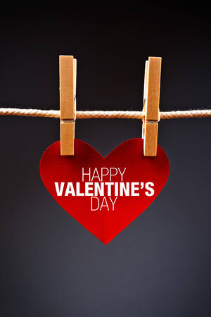 clothes pins: Heart shaped Valentines Day card with message attached to a rope with clothes pins. Romance, love and affection concept.