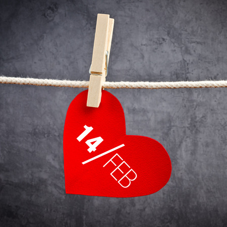 clothes pins: Heart shaped Valentines Day card with date February 14th attached to a rope with clothes pins. Romance, love and affection concept.