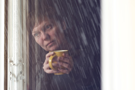 Lonelsome woman drinking cup of coffee by the window of her living room, looking out at rain falling with a sad look on her face. Selective focus with shallow depth of field, shot through the window.