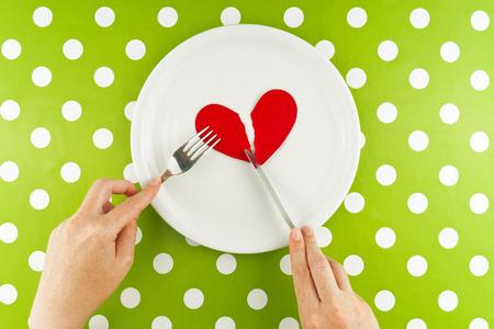 corazon humano: Mujer que come el coraz�n roto en un plato blanco, vista desde arriba.