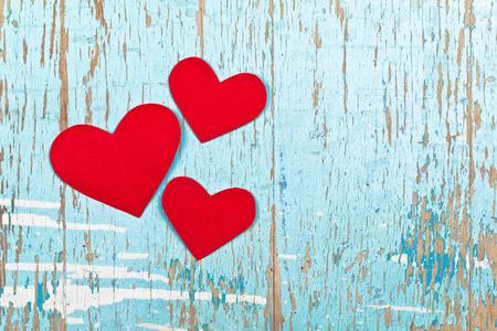 adore: Valentines Day background with red paper hearts on old grunge cyan wood texture as copy space. Complementary colors.