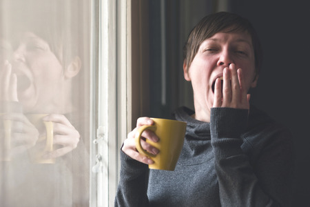 yaw: Beautiful sleepy caucasian adult woman drinking cup of coffee and yawning in the early morning. Selective focus with shallow depth of field. Stock Photo