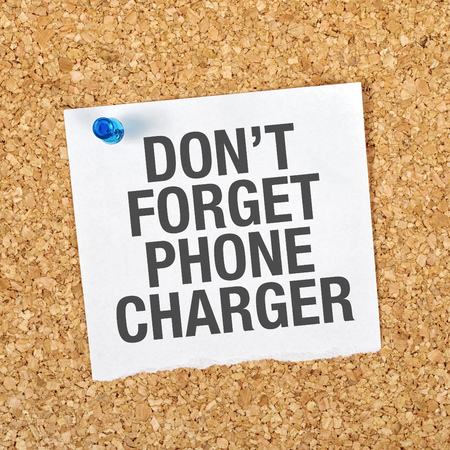 charger: Dont Forget Phone Charger Message on Reminder Note Pinned to a Cork Memory Bulletin Board. Stock Photo