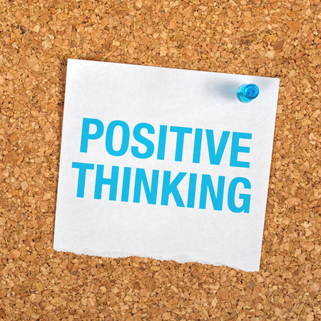 idealism: Positive Thinking Reminder Note Message on Paper Pinned to a Cork Bulletin Board.