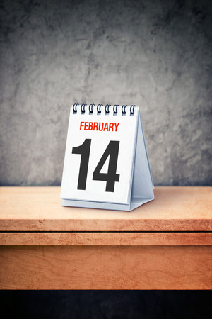 14th: Valentine day concept. February 14th on desk calendar at office table. Reminder of upcoming holiday.