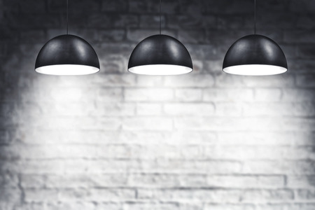 wall bricks: White Brick Wall and Three Ceiling Lamps in room as backdrop Stock Photo