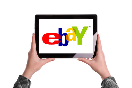 ebay: Novi Sad, Serbia - January 02, 2015: Hands Holding Digital Tablet Computer with Ebay Logo displayed on the screen. Illustrative editorial image isolated on white background.