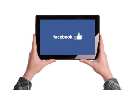 illustrative editorial: Novi Sad, Serbia - January 02, 2015: Hands Holding Digital Tablet Computer with Facebook Logo displayed on the screen. Illustrative editorial image isolated on white background. Editorial