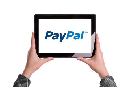paypal: Novi Sad, Serbia - January 02, 2015: Hands Holding Digital Tablet Computer with PayPal Logo displayed on the screen. Illustrative editorial image isolated on white background.