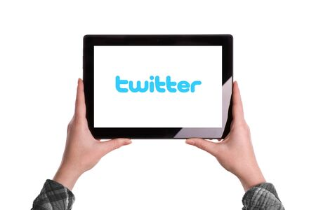illustrative editorial: Novi Sad, Serbia - January 02, 2015: Hands Holding Digital Tablet Computer with Twitter Logo displayed on the screen. Illustrative editorial image isolated on white background. Editorial