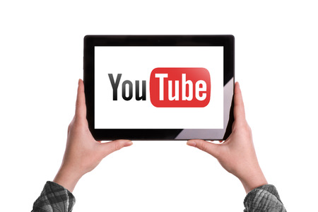 Novi Sad, Serbia - January 02, 2015: Hands Holding Digital Tablet Computer with YouTube Logo displayed on the screen. Illustrative editorial image isolated on white background. Editorial