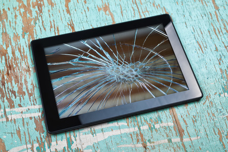 blasted: Digital Tablet Computer with Broken Screen on old wooden table.