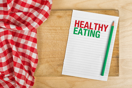 underweight: Heathy Eating Notebook with Pencil on Kitchen Table, Concept of Guidelines for Proper Nutrition with Copy Space.