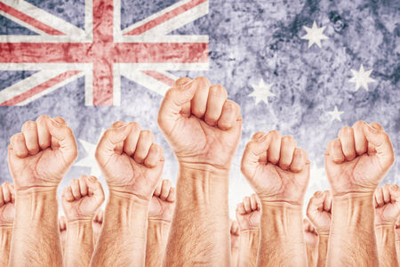 resist: Australia Labour movement, workers union strike concept with male fists raised in the air fighting for their rights, Australian national flag in out of focus background.