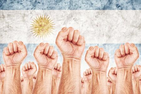 adentro y afuera: Movimiento Argentina del Trabajo, sindicato de trabajadores concepto huelga con los pu�os masculinos planteadas en los combates de aire por sus derechos, la bandera nacional argentina en fondo fuera de foco. Foto de archivo