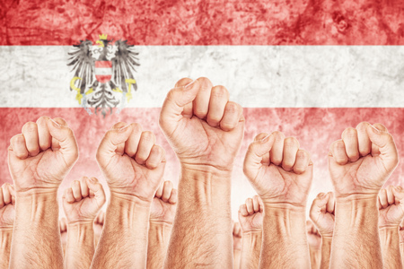 common goals: Austria Labour movement, workers union strike concept with male fists raised in the air fighting for their rights, Austrian national flag in out of focus background.