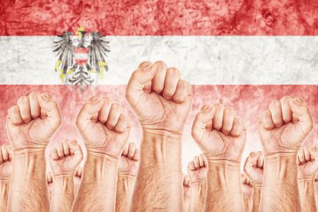 adentro y afuera: Movimiento Austria del Trabajo, sindicato de trabajadores concepto huelga con los pu�os masculinos planteadas en los combates de aire por sus derechos, bandera nacional de Austria en fondo fuera de foco.