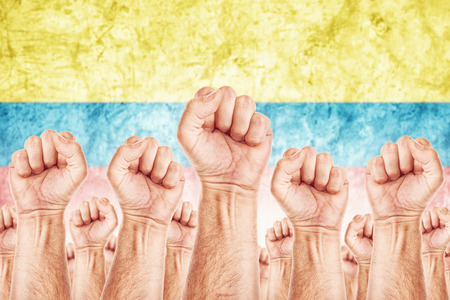 common goals: Columbia Labour movement, workers union strike concept with male fists raised in the air fighting for their rights, Columbian national flag in out of focus background. Stock Photo
