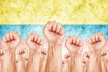 adentro y afuera: Movimiento Columbia del Trabajo, sindicato de trabajadores concepto huelga con los pu�os masculinos planteadas en los combates de aire por sus derechos, bandera nacional Colombina de fondo fuera de foco.