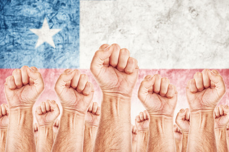 revolt: Chile Labour movement, workers union strike concept with male fists raised in the air fighting for their rights, Chilean national flag in out of focus background.