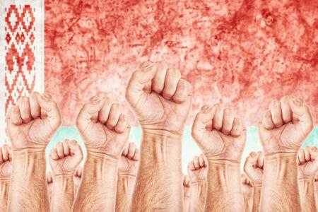 adentro y afuera: Movimiento Bielorrusia Trabajo, sindicato de trabajadores concepto huelga con los pu�os masculinos planteadas en los combates de aire por sus derechos, bandera nacional de Bielorrusia en fondo fuera de foco.