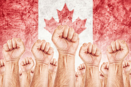 common goals: Canada Labour movement, workers union strike concept with male fists raised in the air fighting for their rights, Canadian national flag in out of focus background.