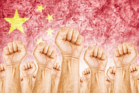common goals: China Labour movement, workers union strike concept with male fists raised in the air fighting for their rights, Chinese national flag in out of focus background. Stock Photo