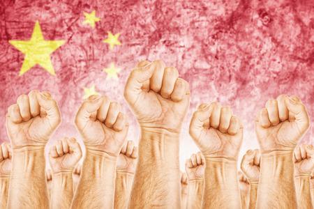 adentro y afuera: Movimiento de China del Trabajo, sindicato de trabajadores concepto huelga con los pu�os masculinos planteadas en los combates de aire por sus derechos, la bandera nacional china en fondo fuera de foco.