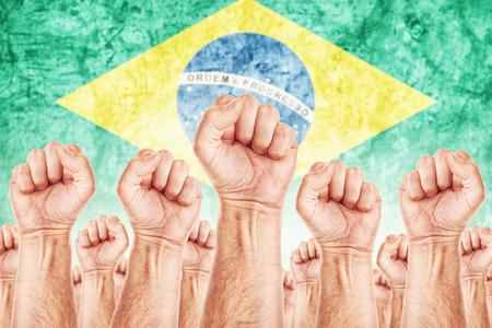 adentro y afuera: Movimiento de Brasil del Trabajo, sindicato de trabajadores concepto huelga con los pu�os masculinos planteadas en los combates de aire por sus derechos, bandera nacional brasile�o en fondo fuera de foco.