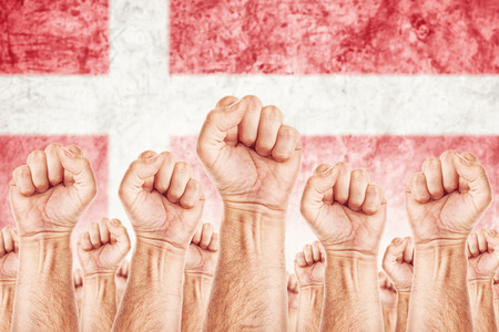 boycott: Denmark Labour movement, workers union strike concept with male fists raised in the air fighting for their rights, Danish national flag in out of focus background.