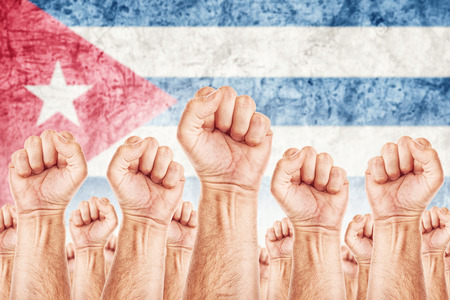 common goals: Cuba Labour movement, workers union strike concept with male fists raised in the air fighting for their rights, Cuban national flag in out of focus background.