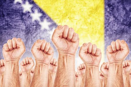 adentro y afuera: Bosnia y Herzegovina Trabajo movimiento, sindicato de trabajadores concepto huelga con los pu�os masculinos planteadas en los combates de aire por sus derechos, bandera nacional de Bosnia en fondo fuera de foco. Foto de archivo