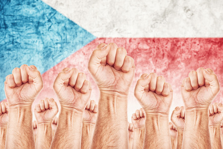 adentro y afuera: Movimiento obrero Checa, sindicato de trabajadores concepto huelga con los pu�os masculinos planteadas en los combates de aire por sus derechos, la bandera nacional de la Rep�blica Checa en fondo fuera de foco.