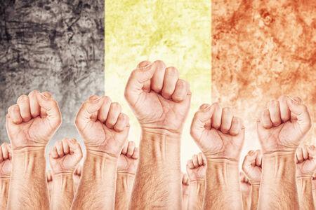 adentro y afuera: Movimiento de B�lgica del Trabajo, sindicato de trabajadores concepto huelga con los pu�os masculinos planteadas en los combates de aire por sus derechos, la bandera nacional en B�lgica de fondo fuera de foco.