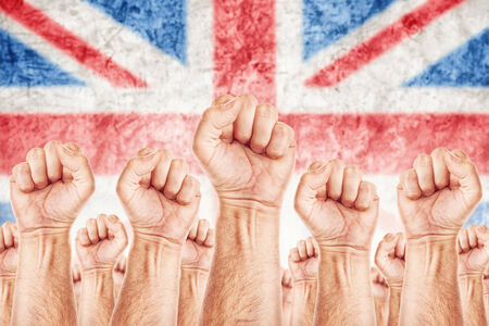 slave labor: Great Britain Labour movement, workers union strike concept with male fists raised in the air fighting for their rights, British national flag in out of focus background.