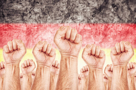 common goals: Germany Labour movement, workers union strike concept with male fists raised in the air fighting for their rights, German national flag in out of focus background.