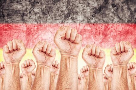 adentro y afuera: Movimiento Alemania del Trabajo, sindicato de trabajadores concepto huelga con los pu�os masculinos planteadas en los combates de aire por sus derechos, bandera nacional alemana en fondo fuera de foco.
