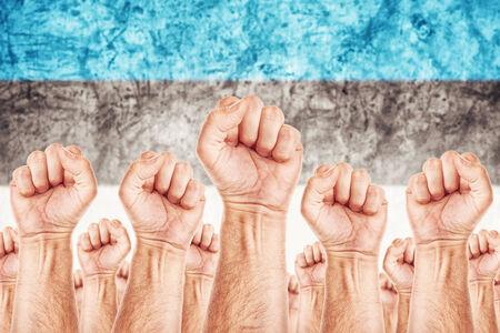 adentro y afuera: Movimiento Estonia Trabajo, sindicato de trabajadores concepto huelga con los pu�os masculinos planteadas en los combates de aire por sus derechos, la bandera nacional de Estonia en fondo fuera de foco.