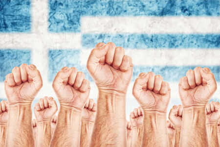 common goals: Greece Labour movement, workers union strike concept with male fists raised in the air fighting for their rights, Greek national flag in out of focus background.