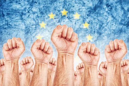 adentro y afuera: Movimiento Europa del Trabajo, sindicato de trabajadores concepto huelga con los pu�os masculinos planteadas en los combates de aire por sus derechos, bandera de la Uni�n Europea en fondo fuera de foco. Foto de archivo