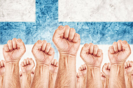 common goals: Finland Labour movement, workers union strike concept with male fists raised in the air fighting for their rights, Finnish national flag in out of focus background.