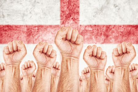 England Labour movement, workers union strike concept with male fists raised in the air fighting for their rights, English national flag in out of focus background. photo