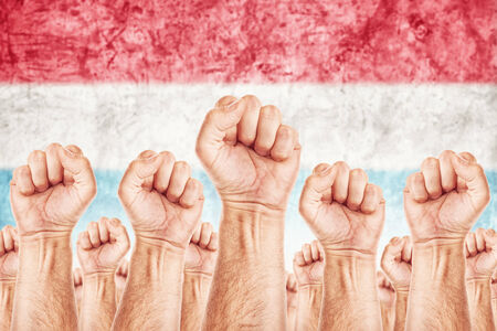 common goals: Netherlands Labour movement, workers union strike concept with male fists raised in the air fighting for their rights, Dutch national flag in out of focus background.