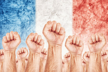 France Labour movement, workers union strike concept with male fists raised in the air fighting for their rights, French national flag in out of focus background. photo