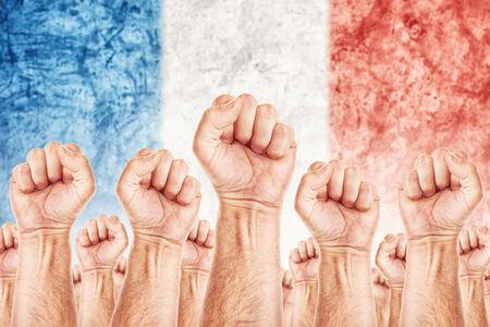 adentro y afuera: Movimiento de Francia del Trabajo, sindicato de trabajadores concepto huelga con los pu�os masculinos planteadas en los combates de aire por sus derechos, la bandera nacional franc�s en fondo fuera de foco. Foto de archivo