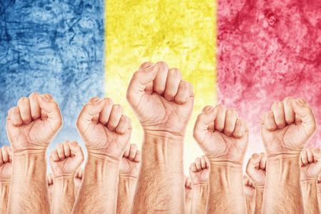 adentro y afuera: Movimiento Rumania del Trabajo, sindicato de trabajadores concepto huelga con los pu�os masculinos planteadas en los combates de aire por sus derechos, la bandera nacional de Rumania en fondo fuera de foco.