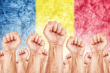syndicate: Romania Labour movement, workers union strike concept with male fists raised in the air fighting for their rights, Romanian national flag in out of focus background. Stock Photo