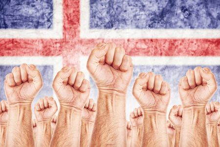common goals: Iceland Labour movement, workers union strike concept with male fists raised in the air fighting for their rights, Icelandic national flag in out of focus background.