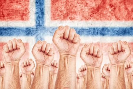 adentro y afuera: Movimiento de Noruega del Trabajo, sindicato de trabajadores concepto huelga con los pu�os masculinos planteadas en los combates de aire por sus derechos, bandera nacional de Noruega en fondo fuera de foco. Foto de archivo
