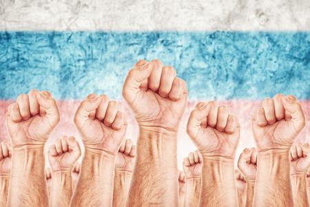 adentro y afuera: Movimiento Rusia del Trabajo, sindicato de trabajadores concepto huelga con los pu�os masculinos planteadas en los combates de aire por sus derechos, bandera nacional rusa en fondo fuera de foco.